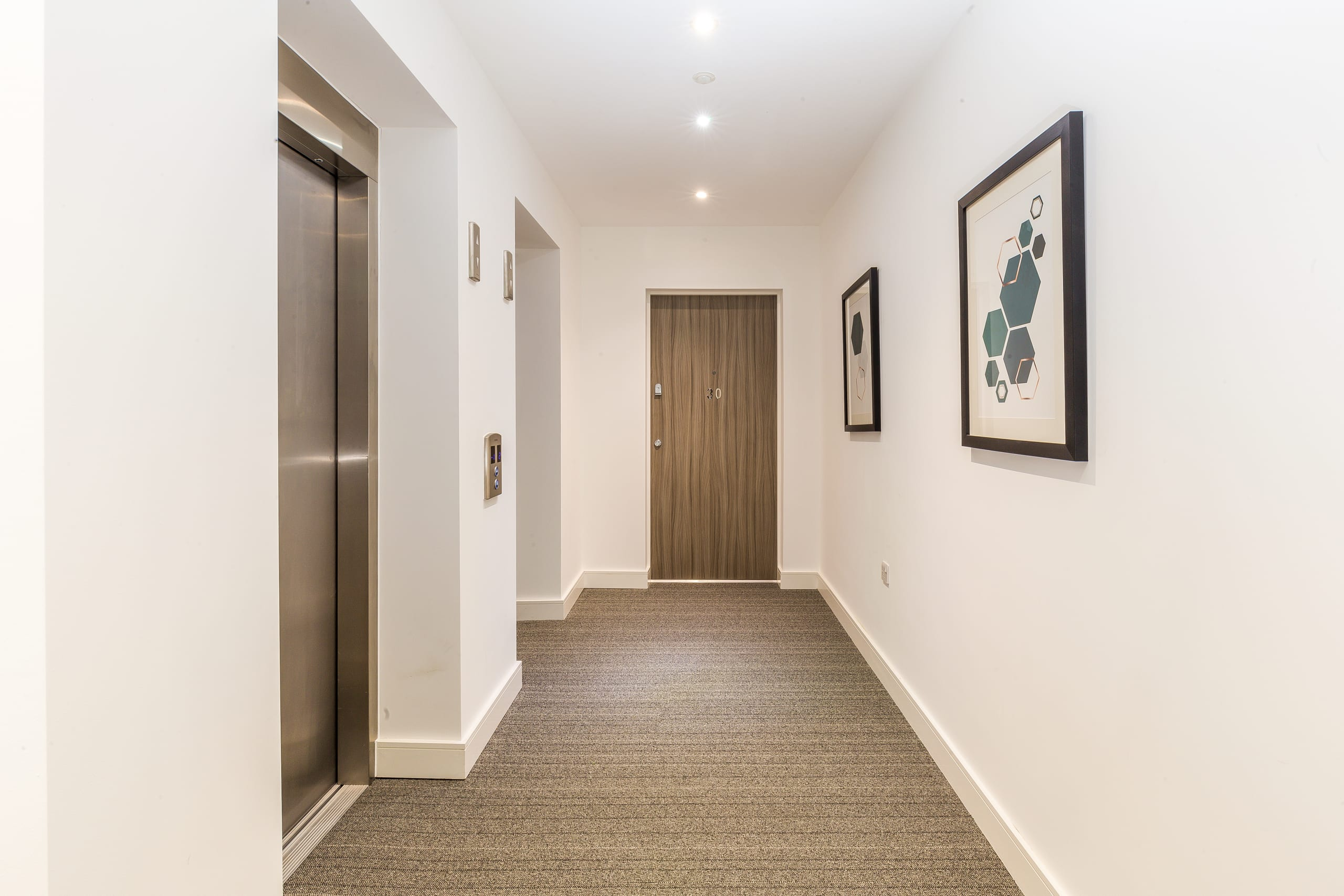 Apartment hallway with white walls and lift system , paintings on the walls